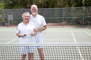 Portrait of active senior couple together on the tennis court.